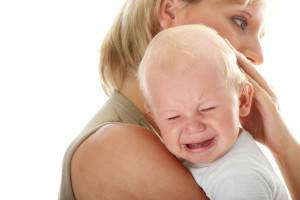 Mother holding her crying baby isolated